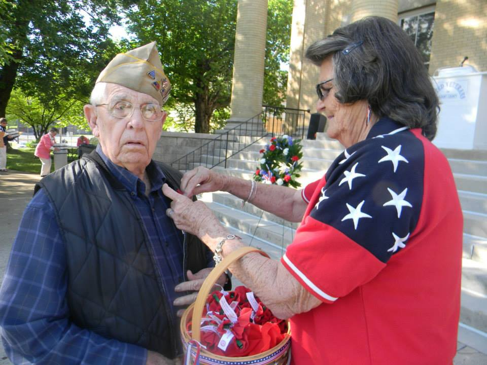 Image of woman pinning red poppy to veteran's lapel